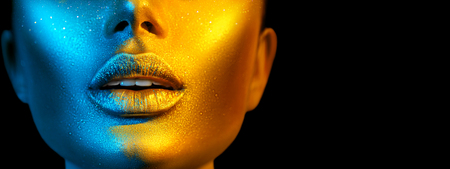 Fashion model woman face in bright sparkles, colorful neon lights, beautiful girl lips. Reklamní fotografie