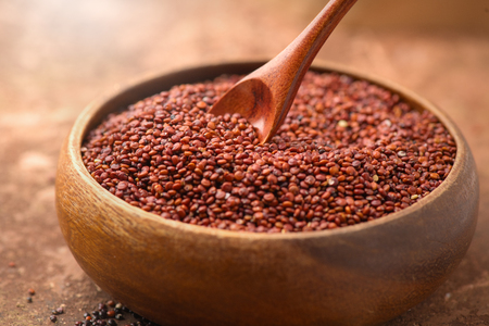 Quinoa. Red, black and white quinoa grains in a wooden bowl.
