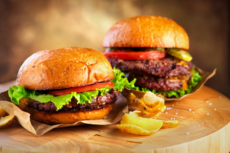 Hamburger and Double Cheeseburger with fries wooden table 스톡 콘텐츠