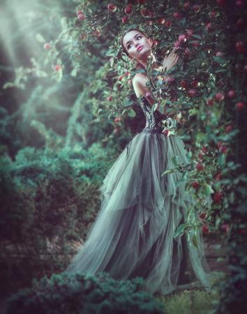 Beauty romantic model girl fashion posing in garden trees, enjoying nature in apple orchard. Beautiful brunette young woman in fantasy Garden, long dress. Outdoor full length portrait. Fairy tail