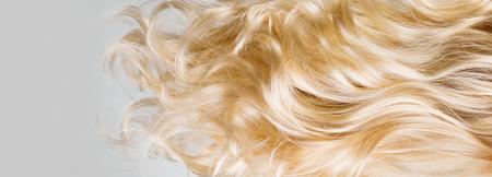 Cabello. Textura hermosa sana del primer del pelo rubio rizado largo. Fondo de cabello rubio ondulado teñido. Concepto de coloración. Cuidado del cabello