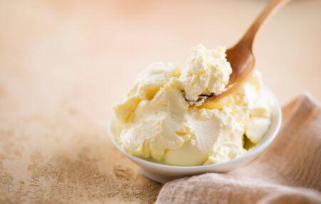 Mascarpone cream cheese closeup. Mascarpone soft milk cream in white bowl. Homemade ice cream, yoghurt Stock Photo