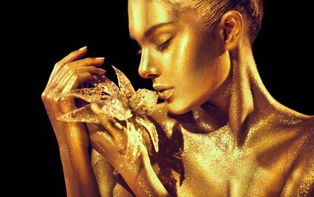 Fashion model woman with bright golden sparkles on skin posing, fantasy flower.