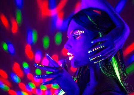 Moda donna discoteca. Modello di ballo in luce al neon, ritratto di ragazza di bellezza con trucco fluorescente. Design artistico