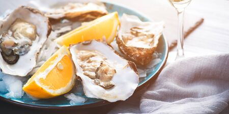 Fresh Oysters closeup, served with oysters, lemon and ice. Healthy seafood. Oyster dinner in restaurant. Gourmet food Stockfoto