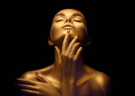 Schönheitsfrau mit goldener Haut. Mode-Kunst-Porträt-Nahaufnahme. Vorbildliches Mädchen mit glänzendem goldenem Berufsmake-up. Goldschmuck