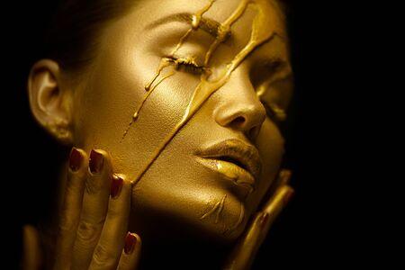 Sexy piękna kobieta ze złotą metaliczną skórą. Z twarzy i ust ściekają smugi złotej farby. Kreatywny makijaż