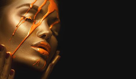 Orange paint smudges drips on woman face. Liquid drops on beautiful model girls mouth, gold metallic skin makeup
