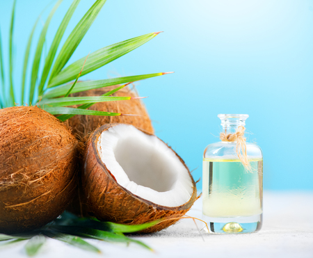 Coconut palm oil in a bottle with coconuts and green palm tree leaf on blue background. Coco nut closeup. Healthy food, skincare concept