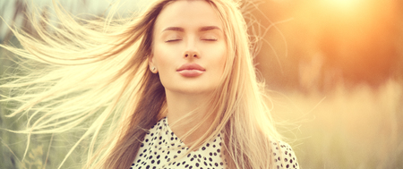 Portrait of beauty girl with fluttering white hair enjoying nature outdoors. Flying blonde hair on the wind. Beautiful young woman face closeup Reklamní fotografie