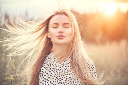 Porträt des Schönheitsmädchens mit dem flatternden weißen Haar, das die Natur draußen genießt. Fliegende blonde Haare im Wind. Schöne junge Frau Gesicht Nahaufnahme Standard-Bild