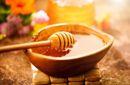 Honey dripping from honey dipper in wooden bowl. Healthy organic thick honey pouring from the wooden honey spoon closeup