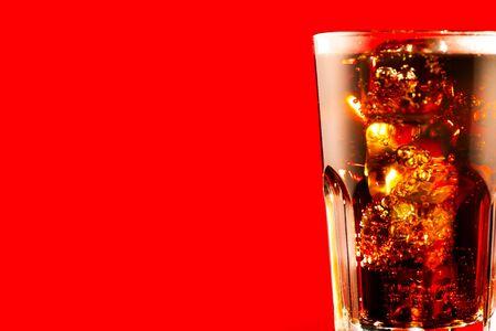 Coca Cola con il primo piano dei cubetti di ghiaccio. Bicchiere di bevanda frizzante marrone su sfondo rosso Archivio Fotografico