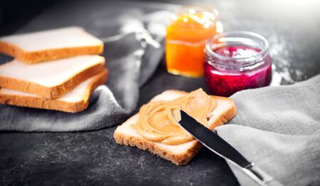 Peanut butter. Making sandwiches with peanut butter and jelly. Natural nutrition and healthy food. American cuisine Stock Photo