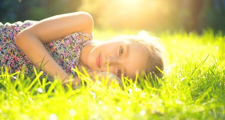 Portrait of a smiling little girl lying on green grass. Cute six years old child enjoying nature in summer park on a lawn