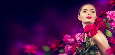 Beauty girl with purple, red, pink peony flowers portrait. Beauty high fashion model woman with peony flowers closeup Фото со стока - 129813494