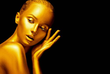 Model girl with shiny golden professional makeup over black. Beauty sexy woman with golden skin. Fashion art portrait closeup. Gold jewellery