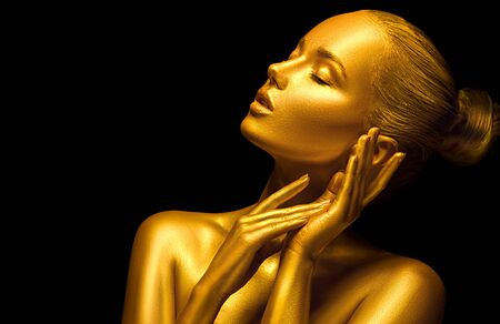 Model girl with shiny golden professional makeup over black. Beauty woman with golden skin. Fashion art portrait closeup. Gold jewellery