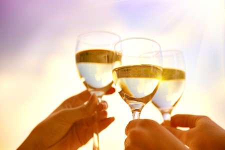People holding glasses of wine, making a toast over sunset sky. Group of friends drinking white wine, toasting. Party outdoors