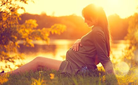 Pregnant woman sitting on green grass, looking on river on sunset, touching her belly. Enjoying healthy pregnancy Фото со стока