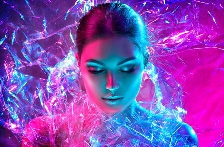 Fashion model woman in colorful bright neon lights posing in studio through transparent film. Portrait of beautiful sexy girl in UV. Art design colorful makeup Stock Photo