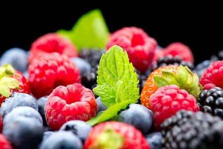Berries. Various colorful berries background. Strawberry, raspberry, blackberry, blueberry closeup over black. Healthy eating