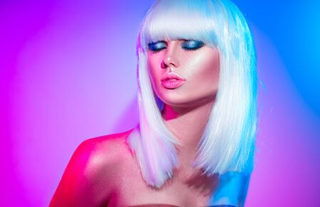 Fashion model girl in colorful bright sparkles and neon lights posing in studio. Portrait of beautiful woman. White hair, trendy glowing makeup
