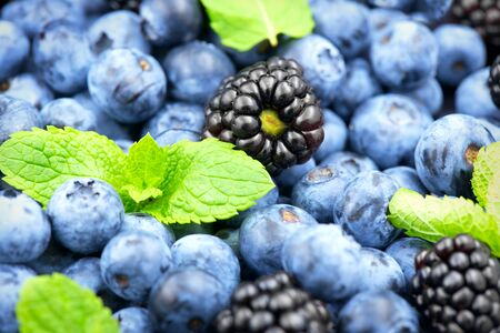 Blueberry and blackberry background. Ripe and juicy fresh picked blueberries closeup Imagens