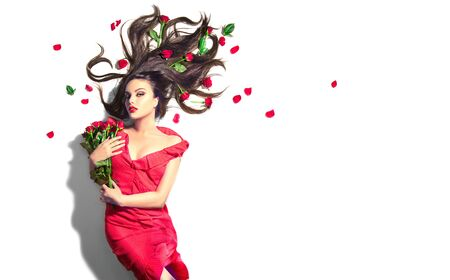 Beauty Sexy Model girl lying on white  with red rose flowers in her hair and a bunch. Stock Photo