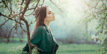 Beauty young woman enjoying nature in a garden, Happy Beautiful brunette girl in foggy Garden with trees.