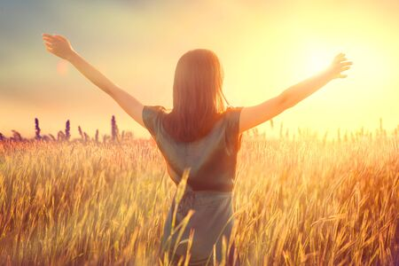 Happy autumn woman raising hands over sunset sky, enjoying life and nature. Imagens