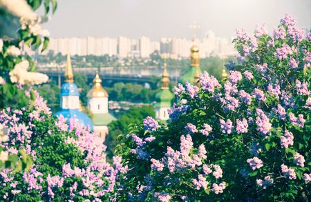 Kyiv city panoramic view with blooming lilac flowers and Orthodox churches on the banks of Dnipro River