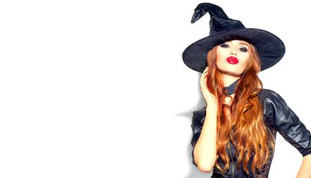 Halloween Sexy Girl wearing witch costume with a hat. Party, Celebrating. Beauty Woman with long red hair and holiday bright make-up isolated on white background. Leather dress