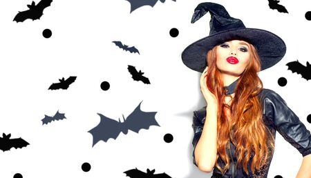 Halloween Sexy Girl wearing witch costume with a hat. Party, Celebrating. Beauty Woman with long hair and holiday bright make-up isolated on white background with bats