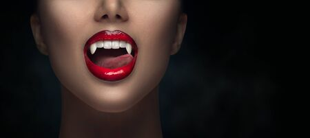 Sexy Vampire Woman's red bloody lips close-up. Vampire girl licking fangs with tongue. Fashion Glamour Halloween art design. Close up of female vampire mouth, teeth. Isolated on black background Zdjęcie Seryjne - 130585486