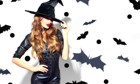 Halloween Sexy Girl wearing witch costume with a hat and Black leather dress. Party, Celebrating. Beauty Woman with long hair and holiday bright make-up isolated on white background with bats Stock Photo