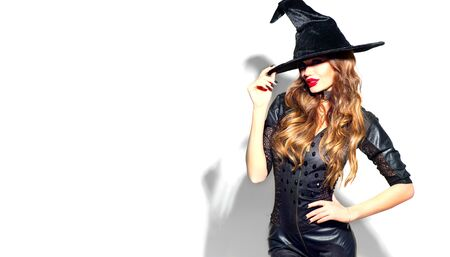 Halloween Sexy Girl wearing witch costume with a hat. Party, Celebrating. Beauty Woman with long hair and holiday bright make-up isolated on white background