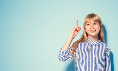 Beauty funny blonde teenage girl has an idea, pointing finger, showing empty copy space for text, blue background. Happy girl presenting point. School girl Proposing product. Advertisement gesture