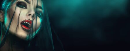 Portrait de femme vampire Halloween avec voile noir sur un visage. Beauté Sexy Vampire Girl avec des dents, des lèvres rouges sanglantes. Maquillage de vampire Conception d'art de mode. Maquillage de fille modèle mystérieux. Crocs. Ténèbres Banque d'images