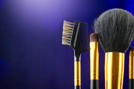 Make-up Brushes set over black holiday blinking background. Various Professional makeup brush on dark backdrop in studio. Make up artist tools Stock Photo