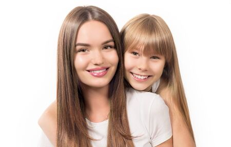 Two sisters - older and younger together. Portrait of beautiful young sisters teenage and adult girls hugging and smiling together, Isolated on white background. Beautiful Siblings, Happy family