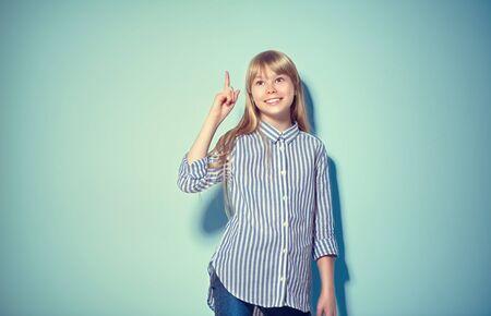 Belleza divertida rubia adolescente tiene una idea, señalar con el dedo, mostrando el espacio vacío de la copia para el texto, fondo azul. Punto de presentación de niña feliz. Niña de la escuela que propone producto. Gesto publicitario Foto de archivo