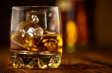 Whiskey with ice cubes. Glass of Whisky and the bottle on wooden table over dark background. Glass of rum alcohol close-up. Cognac closeup, Spirits drink, cocktail Stok Fotoğraf