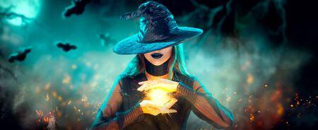 Chica bruja de Halloween con hacer brujería, magia en sus manos, hechizos. Hermosa mujer joven con sombrero de brujas conjurando. Fondo de bosque mágico oscuro espeluznante. Mago. Amplio diseño de arte de fiesta de Halloween. Foto de archivo