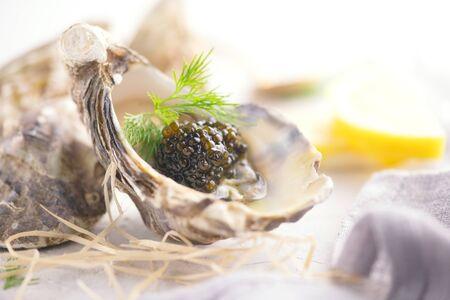 Frische Austern mit schwarzem Kaviar. Geöffnete Austern mit schwarzem Störkaviar und Zitrone, Gourmetessen im Restaurant. Feinkostgericht Nahaufnahme