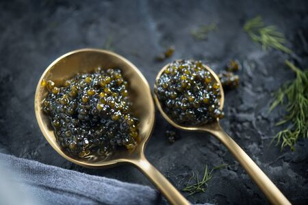 Black Caviar in a spoon on dark background. High quality real natural sturgeon black caviar close-up. Delicatessen. Texture of expensive luxury caviar. Food Backdrop. Top view, flatlay Zdjęcie Seryjne - 131366159