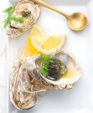 Fresh oysters with black caviar. Opened oysters with black sturgeon caviar and lemon, Gourmet food in restaurant. Delicatessen dish. Served table. Top view, flatlay Archivio Fotografico