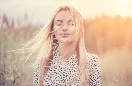 Close Up Ritratto di ragazza di bellezza con svolazzanti capelli bianchi che si gode la natura all'aperto, su un campo. Capelli biondi al vento. Brezza che gioca con i capelli della ragazza. Bello primo piano del fronte della giovane donna