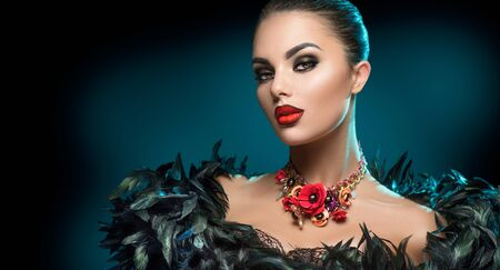 High Fashion Model Girl Portrait with Trendy gothic make-up, Black Hair style, Make up, dark accessories. Halloween Vampire Woman portrait with black smoky eyes, feathers dress, over black background 写真素材