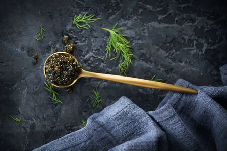 Black Caviar in a spoon on dark background. High quality real natural sturgeon black caviar close-up. Delicatessen. Texture of expensive luxury caviar. Food Backdrop. Top view, flatlay Zdjęcie Seryjne